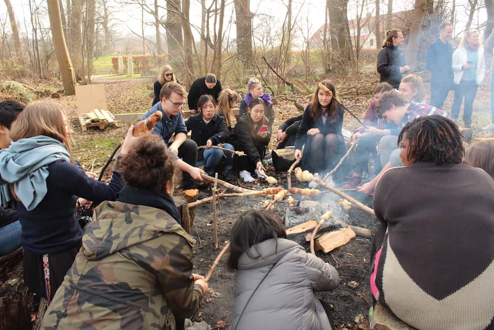 students are making traditional Danish bred around the fire.