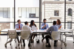 Business team look to manager at meeting in open plan office