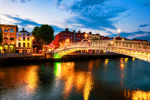 Night view of famous illuminated Ha Penny Bridge in Dublin, Ireland at sunset