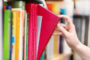 closeup hand selecting book from a bookshelf