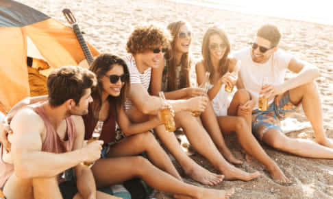 Group of cheerful happy friends camping at the beach, drinking beer
