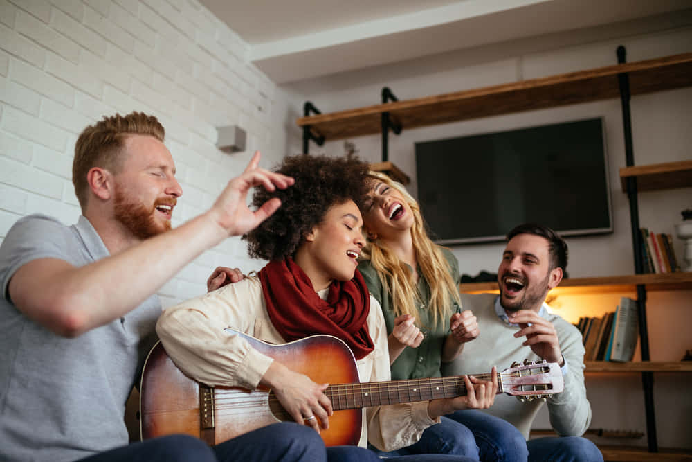 Friends at home enjoying singing and playing guitar.